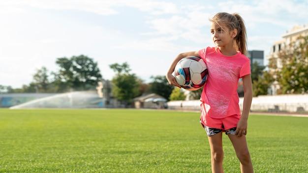 Vista dianteira, de, menina, segurando bola Foto gratuita