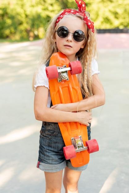 Vista dianteira, de, menina, segurando, skateboard Foto gratuita
