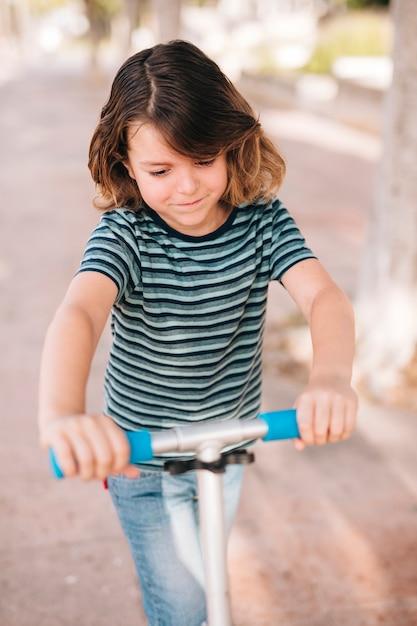 Vista dianteira, de, menino, com, scooter Foto gratuita