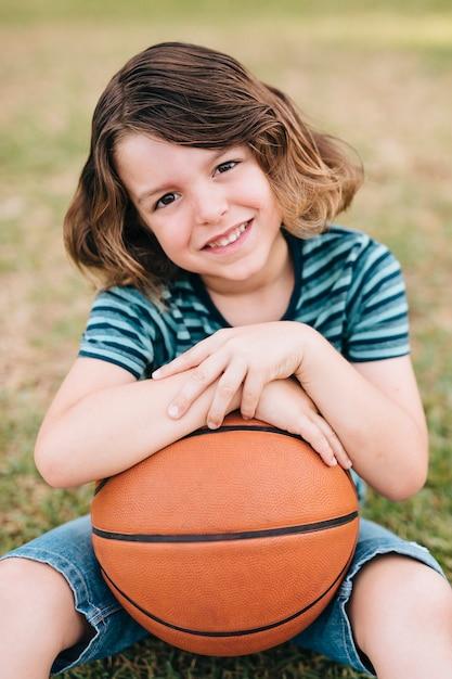 Vista dianteira, de, menino, segurando basquetebol Foto gratuita