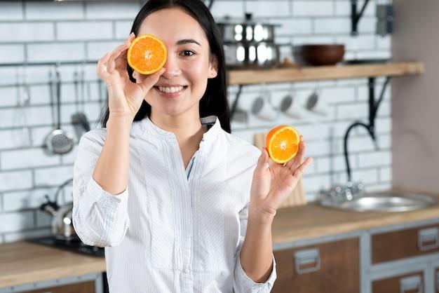 Vista dianteira, de, mulher asian, cobertura, dela, um olho, com, fatia laranja, em, cozinha Foto gratuita