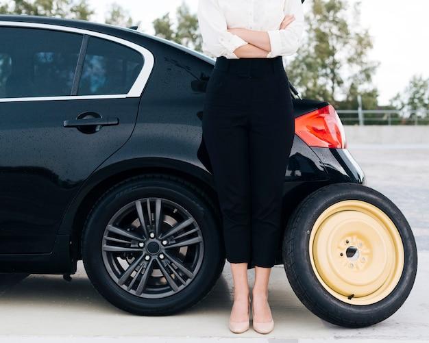 Vista dianteira, de, mulher, com, sobressalente, pneu Foto gratuita