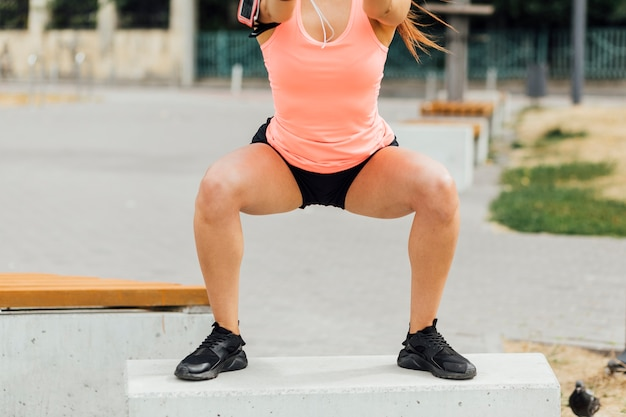 Vista dianteira, de, mulher, fazendo, crouching, exercícios Foto gratuita