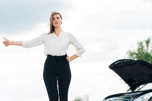 Vista dianteira, de, mulher, hitchhiking Foto gratuita