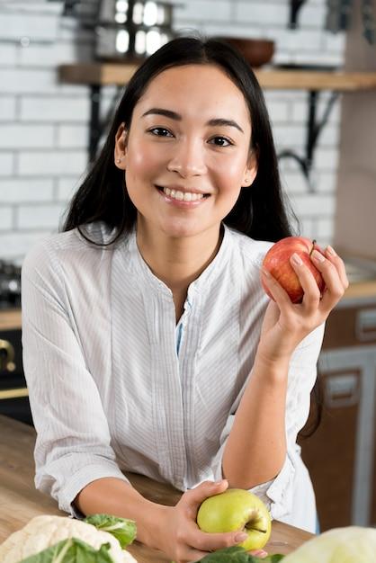 Vista dianteira, de, mulher sorridente, segurando, maçãs, olhando câmera Foto gratuita