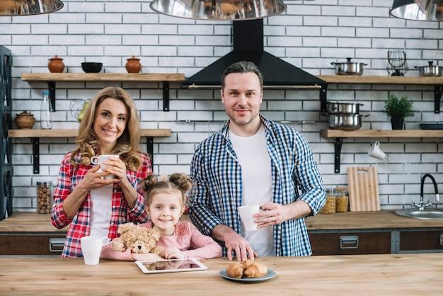 Vista dianteira, de, sorrindo, família, tendo, café manhã, em, cozinha Foto gratuita