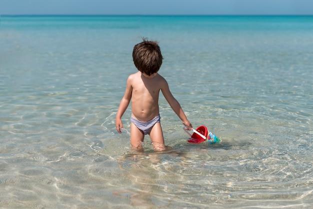 Vista dianteira, de, um, pequeno, criança, tocando, em, água Foto gratuita