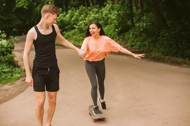 Vista dianteira, menino, ajudando, menina, skateboarding Foto gratuita