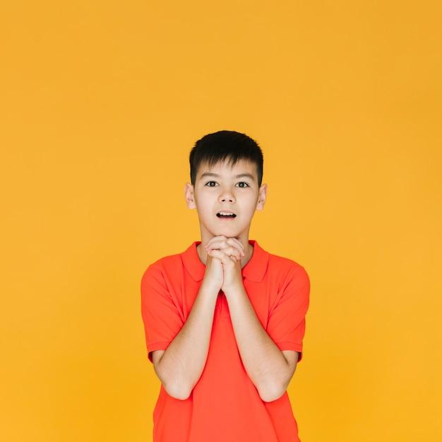 Vista dianteira, menino jovem, orando Foto gratuita