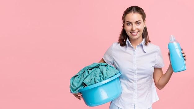 Vista dianteira, mulher, segurando, cesta lavanderia, e, detergente Foto gratuita