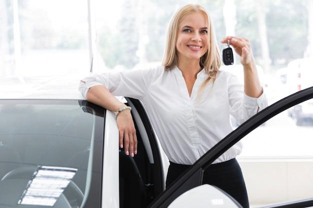 Vista dianteira, tiro, com, um, mulher jovem, segurando, tecla carro Foto gratuita