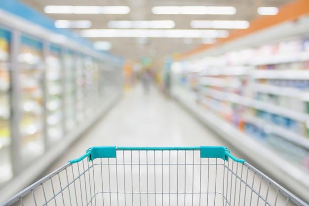 Vista do carrinho de compras com desfoque abstrato do corredor do supermercado congelados e produtos lácteos no fundo das prateleiras da geladeira Foto Premium