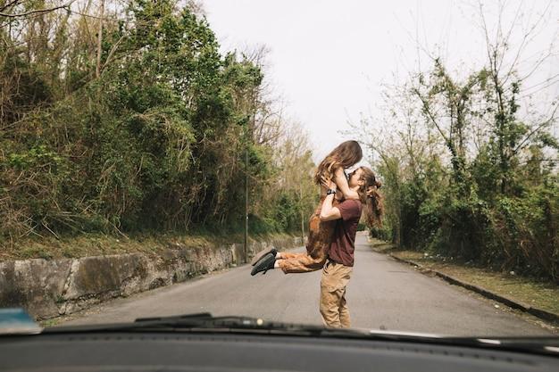 Vista do carro do jovem casal no meio da estrada Foto gratuita