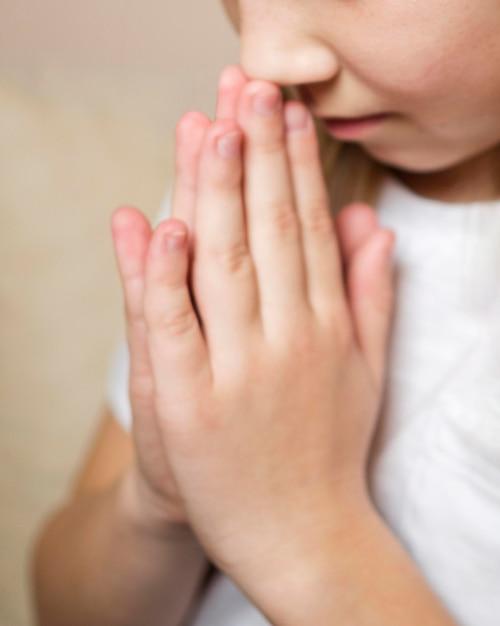 Vista do close-up da menina rezando Foto gratuita