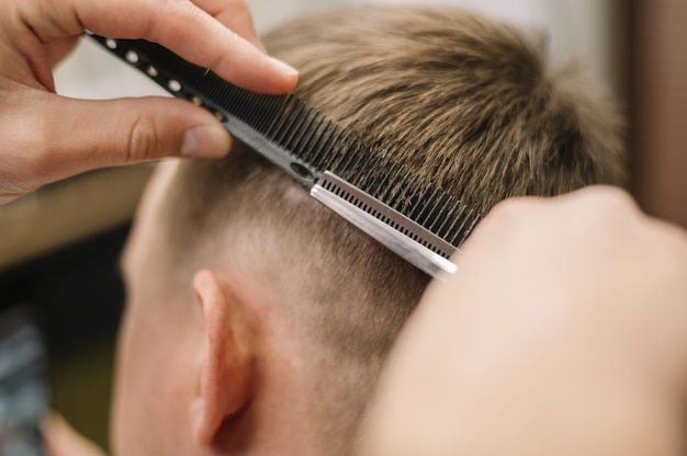 Vista do close-up de cabeleireiro dando um corte de cabelo para um cliente Foto gratuita