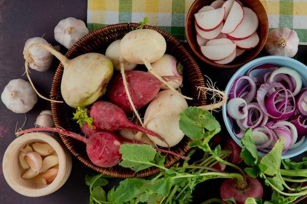 Vista do close-up de cesta e tigelas cheias de legumes como cebola rabanete e alho em fundo marrom Foto gratuita