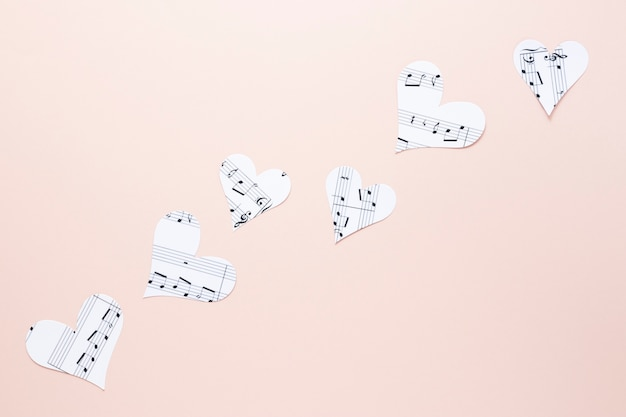 Vista do close-up de corações com notas musicais no fundo liso Foto gratuita