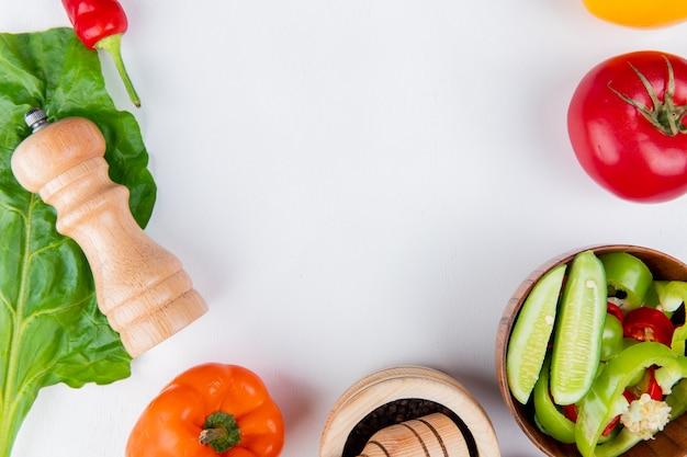 Vista do close-up de legumes como tomate pimenta com sal de salada de legumes e deixe na mesa branca com espaço de cópia Foto gratuita