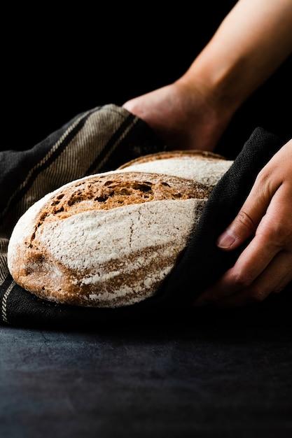 Vista do close-up de mãos segurando um pão Foto gratuita