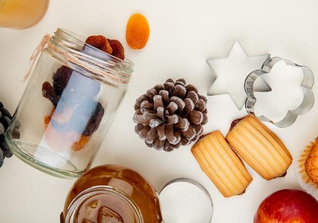 Vista do close-up de passas derramando fora da jarra e pinha com geléia de pêssego e biscoitos na mesa branca Foto gratuita