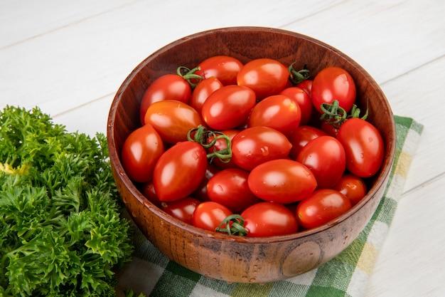 Vista do close-up de tomates em uma tigela com coentro chinês no pano na mesa de madeira Foto gratuita