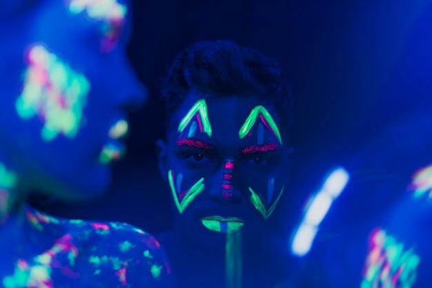 Vista do close-up do homem com maquiagem fluorescente Foto gratuita