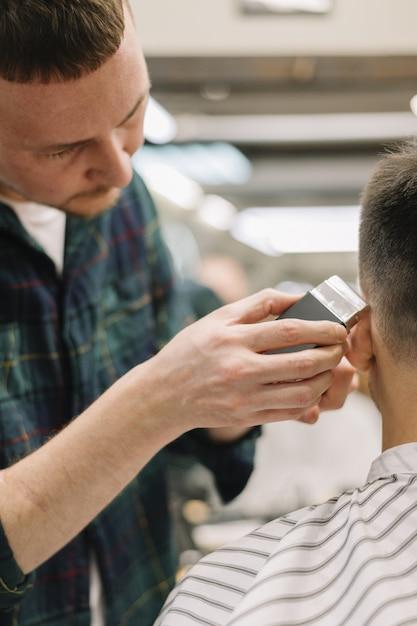 Vista do close-up do homem cortando o cabelo Foto gratuita