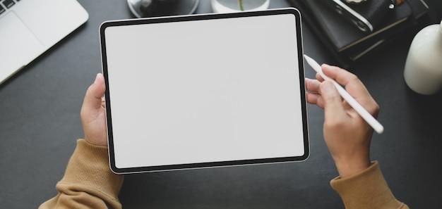 Vista do close-up do homem usando o tablet de tela em branco enquanto trabalhava no local de trabalho moderno escuro Foto Premium
