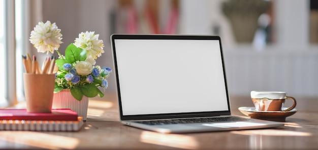Vista do close-up do local de trabalho confortável com mock-se computador portátil e material de escritório na mesa de madeira Foto Premium