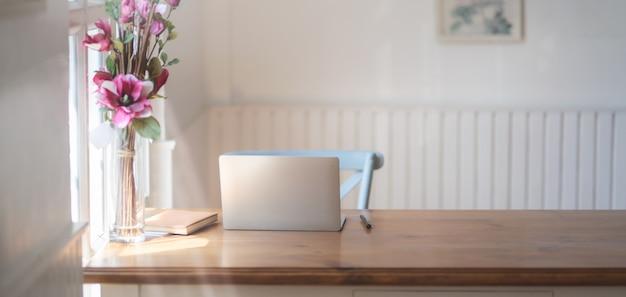 Vista do close-up do local de trabalho confortável com mock-se computador portátil, material de escritório e vaso de flor rosa na mesa de madeira Foto Premium