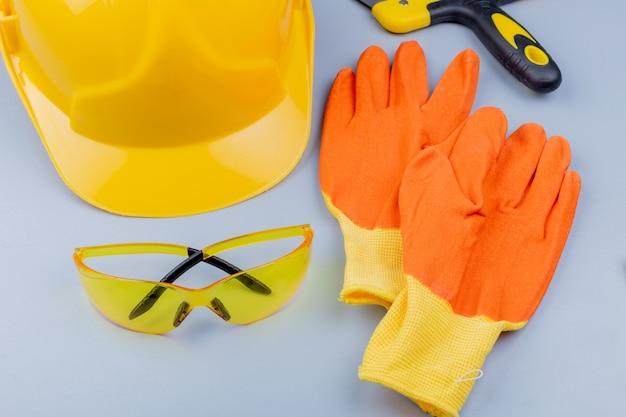 Vista do close-up do padrão do conjunto de ferramentas de construção, como óculos de segurança, capacete de segurança, espátula e luvas em fundo cinza Foto gratuita