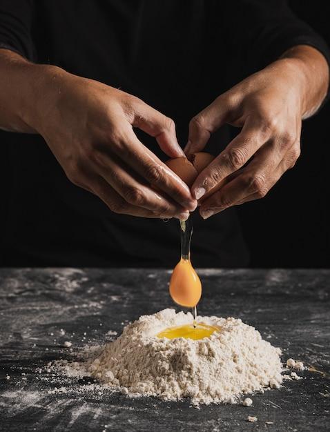 Vista do close-up, misturando ovo com farinha para composição da massa Foto gratuita