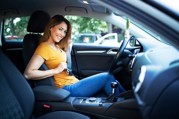 Vista do interior do carro de motorista feminina colocando o cinto de segurança Foto gratuita