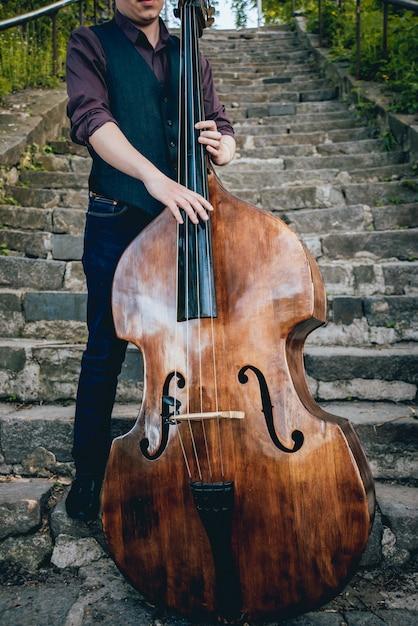 Vista do músico tocando contrabaixo na rua Foto Premium