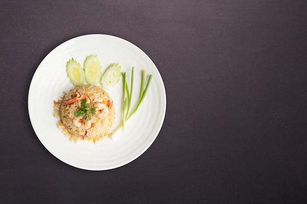 Vista do topo. arroz frito com camarão em prato redondo branco isolado no fundo preto de pedra da natureza. conceito de comida tailandesa Foto Premium
