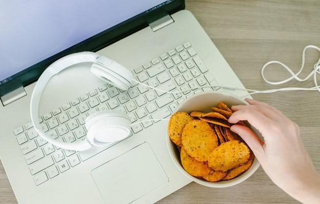 Vista do topo do laptop, fones de ouvido e mãos femininas com chips Foto Premium