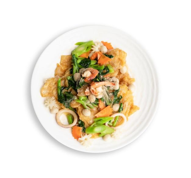 Vista do topo. macarrão frito com frutos do mar e vegetais em prato redondo branco isolado no branco. conceito de comida tailandesa Foto Premium