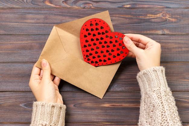 Vista do topo. mão da menina que escreve a carta de amor no dia de valentim de saint. Foto Premium
