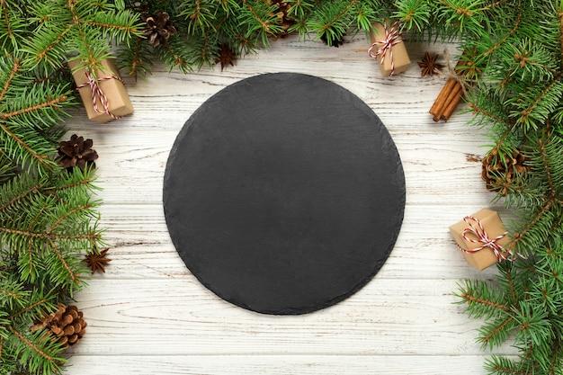 Vista do topo. placa de ardósia preta vazia na madeira Foto Premium
