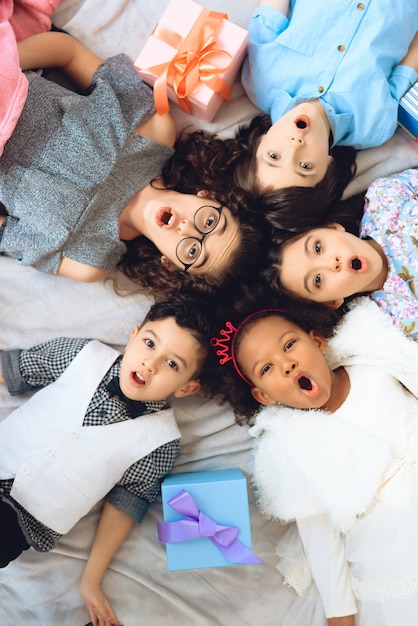 Vista do topo. retrato das crianças alegres que se encontram no assoalho. Foto Premium