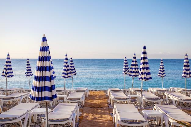Vista dos guarda-chuvas listrados azuis na praia de nice, cote d'azur, sul da frança Foto Premium