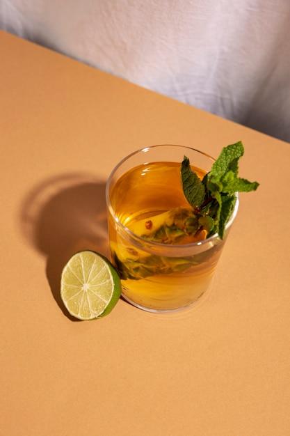 Vista elevada da bebida cocktail com limão cortados ao meio sobre a mesa marrom Foto gratuita