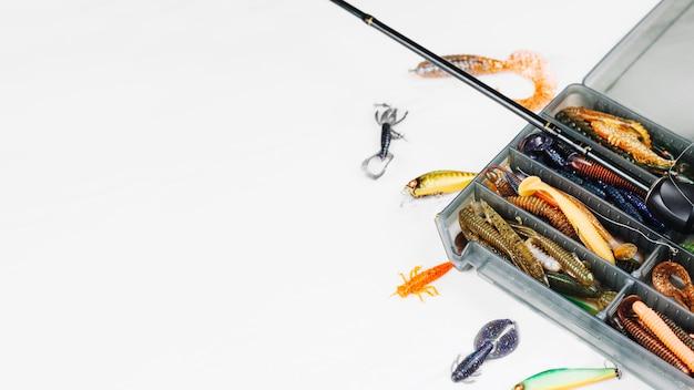 Vista elevada da caixa de isca com vara de pescar no fundo branco Foto gratuita