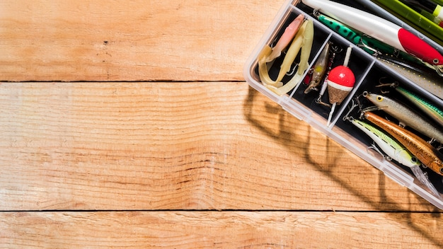 Vista elevada da isca de pesca e pesca flutua no recipiente na mesa de madeira Foto gratuita