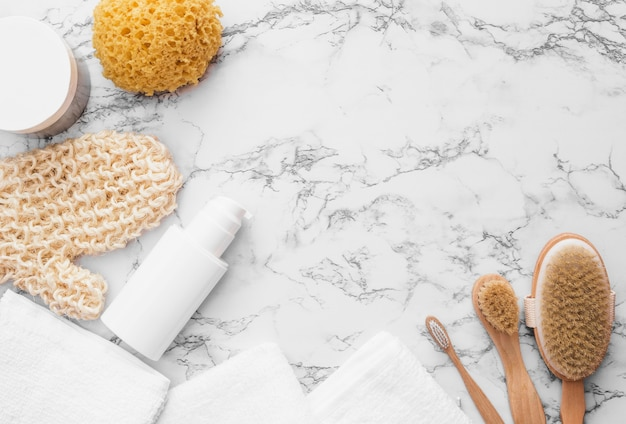 Vista elevada da luva; esponja; escova; toalha e creme hidratante em fundo de mármore Foto gratuita