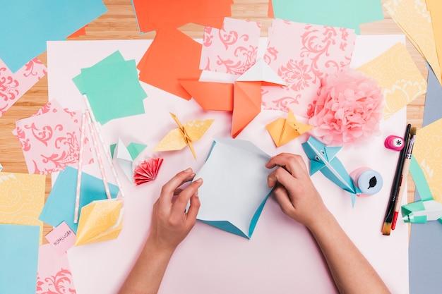 Vista elevada da mão humana, fazendo arte de papel origami na mesa de madeira Foto gratuita