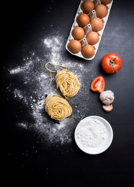 Vista elevada da massa de capellini com caixa de ovos; tomate suculento; alho e tigela de farinha sobre o balcão Foto gratuita