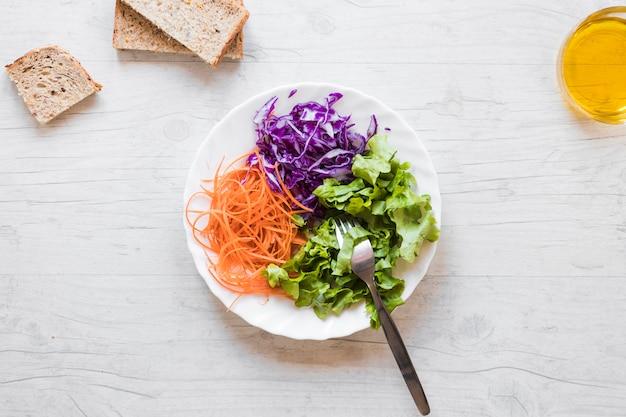 Vista elevada da salada saudável com garfo; fatias de óleo e pão contra a mesa de madeira Foto gratuita