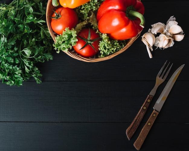 Vista elevada da salsa; pimentão; tomate; alface; dentes de alho e utensílios de cozinha na superfície preta Foto gratuita
