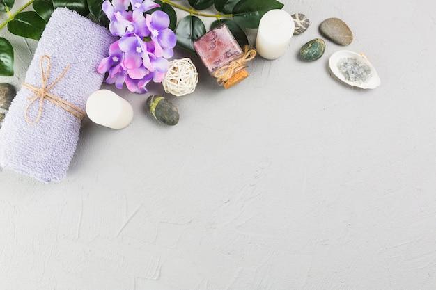 Vista elevada da toalha; velas; mamadeira; flores e pedras spa em pano de fundo cinzento Foto gratuita